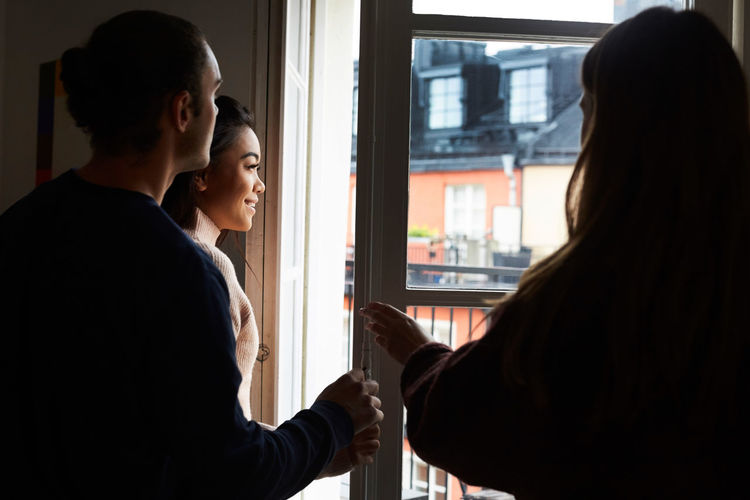 Side view of a young woman standing against window