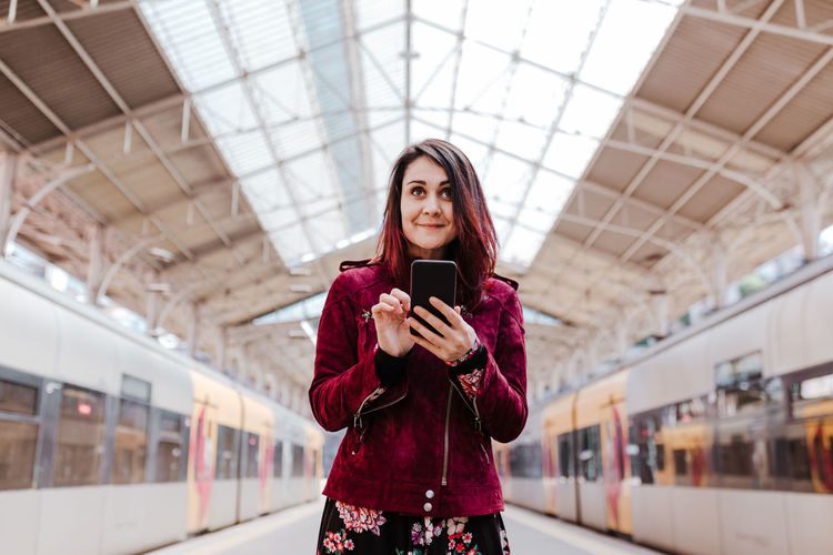 Full length of young woman using mobile phone
