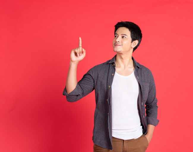 Young man looking away against red background