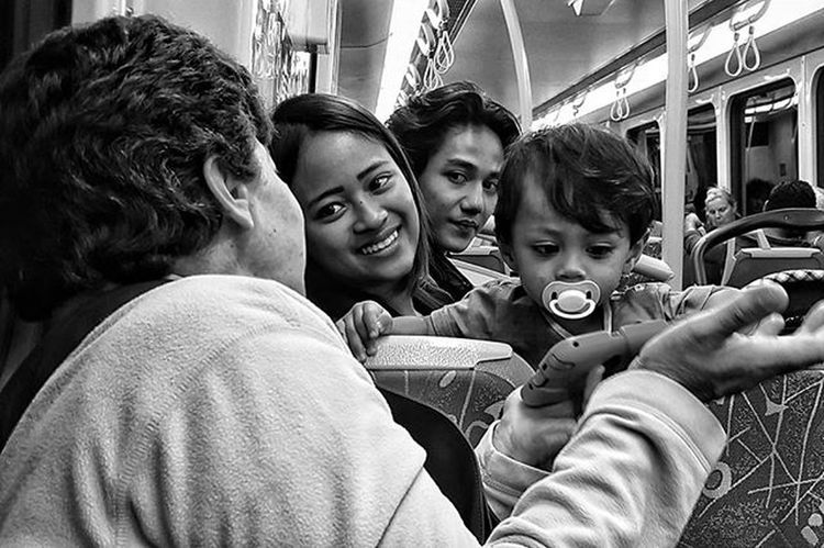 Beautiful moments shared with strangers. . Entering into this Easter Long weekend. I wanted to share this story with you. The older lady was sitting on the train debating with her friends accross the isle... and this baby dropped into her lap. While his mothers attention was distracted he climbed over the back of the chair, landing in her lap! He looked up at her with his big eyes and showed her the game on his tablet. While the mother was horrified... this tough Gran turned to butter and honey... she was so animated playing with the baby. He kept jumping back and fourth helped now by both sides... and when it was time to leave he kept waving at his new Gran until she was out of sight. A connection, from the trusting innocence of a child. It's beautiful. When I see them on the train now, they sit near together so they can play, and Mum fills Gran in on everything that he's been getting up to since they last saw each other. It's become one of my all-time favourite Transport Reality Show... I tune in as much as I can. (This photo is from the very 1st meeting) Blackandwhite Blackandwhitephotography Blackandwhitelove Insta_bw Bnw_society Bnw Bnw_australia Bnw_captures Bnw_city EyeEm Eyeemphoto Justgoshoot Streetlife_mag Main_vision Profile_vision Justgoshoot Bnw_city The_lady_bnw Rsa_bnw