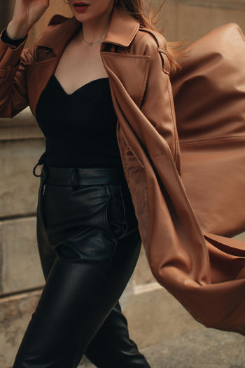 Cropped figure of young woman wearing stylish brown overcoat and black outfit. street casual autumn