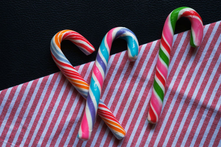 High angle view of fresh colorful candy canes on striped napkin against black background