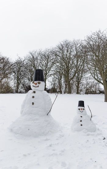 Snowmen in a field of snow Bare Tree Cold Temperature Day Nature No People Outdoors Snow Snowman Snowmen Tree White Color Winter