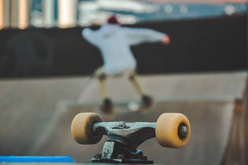 Skateboard wheels with man performing stunt in background