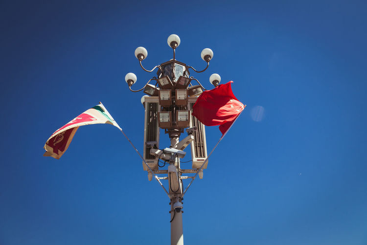 Low angle view of flags on gas light against clear blue sky at forbidden city