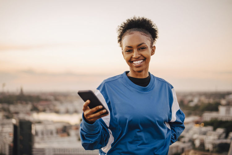 Portrait of smiling man standing on mobile phone against sky