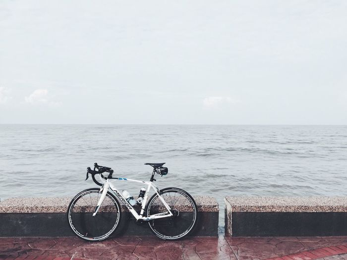 Bicycles parked by sea against sky