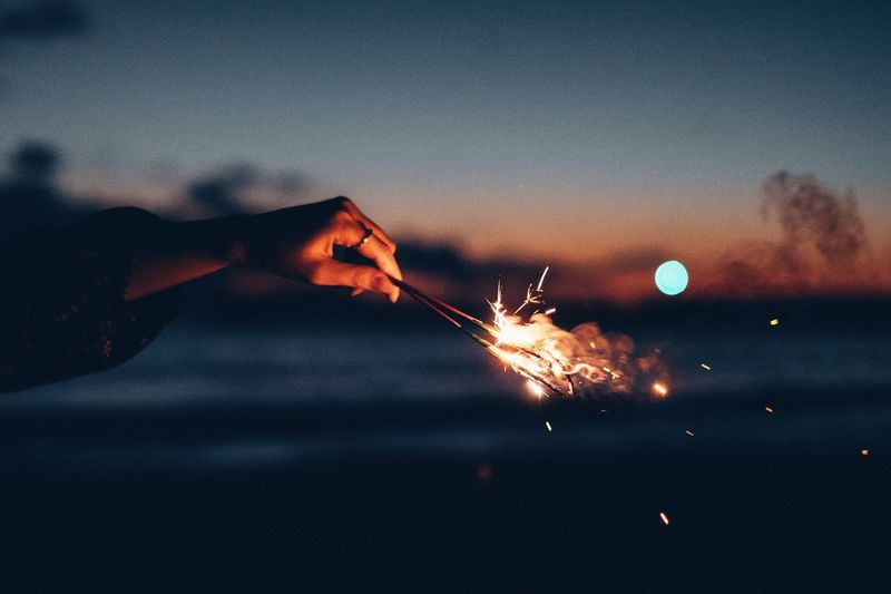 Cropped hand holding burning sparkler at sunset against sky