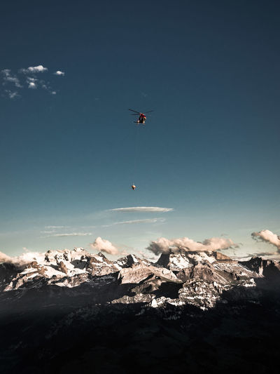 Flying Sky Mid-air Beauty In Nature Scenics - Nature Nature Mountain Snow Winter Day Adventure Solid Rock Sport Rock - Object Cold Temperature Non-urban Scene Extreme Sports Tranquil Scene Outdoors Helicopter