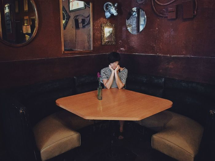 Depressed young woman with hands on chin sitting in restaurant