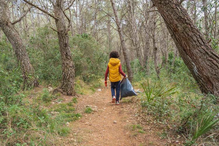 Rear view of boy walking with garbage bag in forest