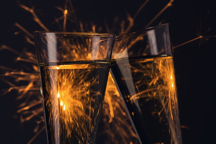Close-up of firework display seen through drinking glasses at night