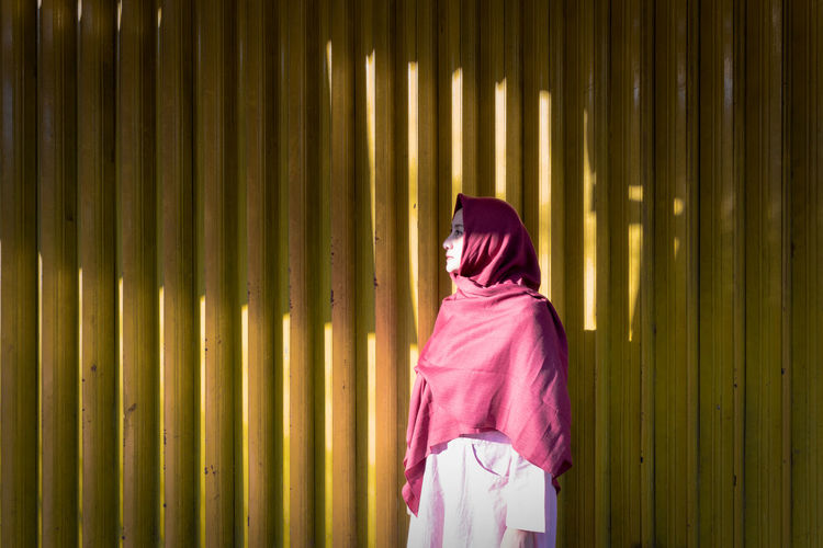 Woman wearing headscarf while standing against yellow corrugated iron