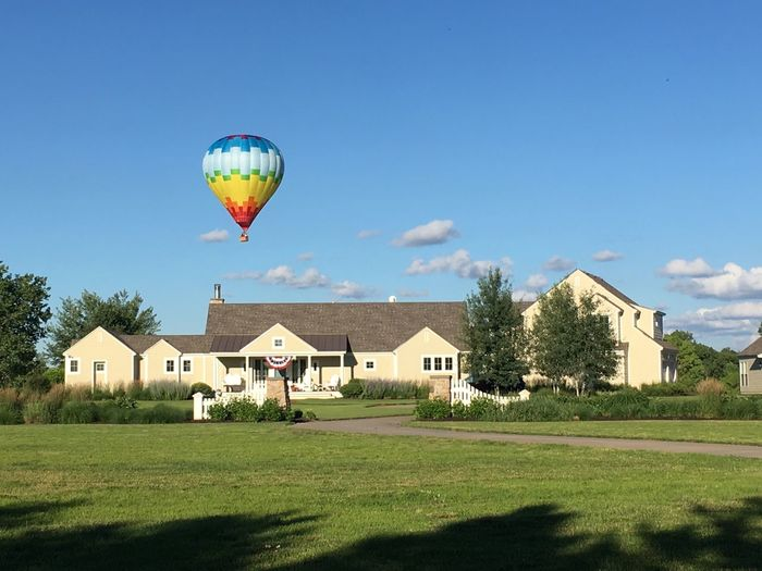 Low angle view of a hot air balloon flying in the clear blue sky next to a house. Building Exterior Architecture Balloon Plant Sky Hot Air Balloon Flying House Tree Residential District Landscape No People Outdoors Copy Space Open Space Green Fields Sunlight Low Angle View Adventure Freedom One Man Only Journey Recreational Pursuit Excitement Nebraska