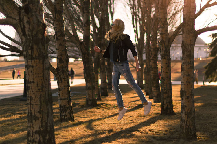 Woman jumping amidst trees