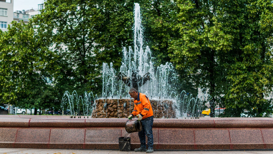 Side view of male worker pouring water in bucket by fountain