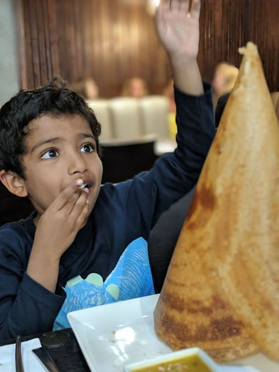 Surprised boy looking at large dosa while sitting at restaurant