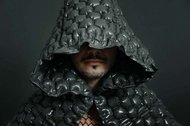 Man wearing hooded cloth against gray background