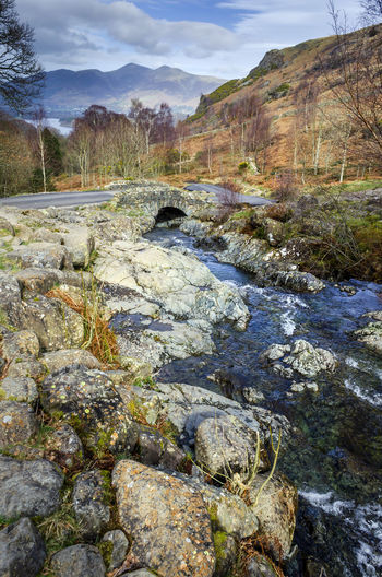 Surface level of stream amidst rocks against sky
