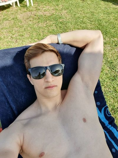 Portrait of shirtless man wearing sunglasses while lying on towel over grass