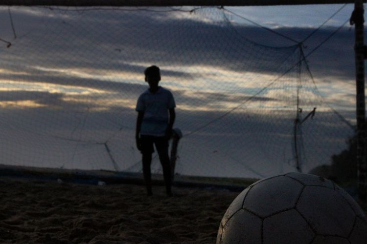 Man playing soccer ball on beach against sky during sunset