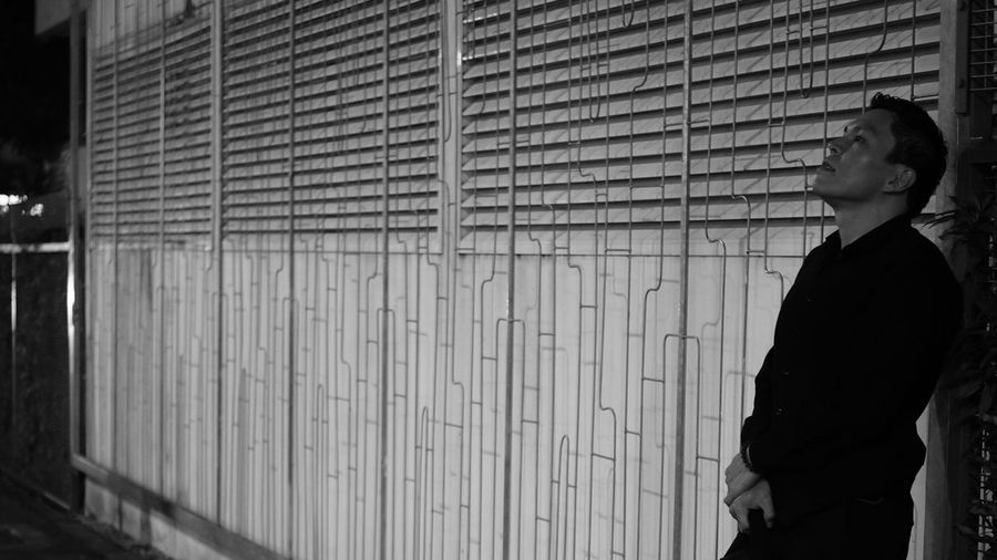 Man looking away while leaning on wall