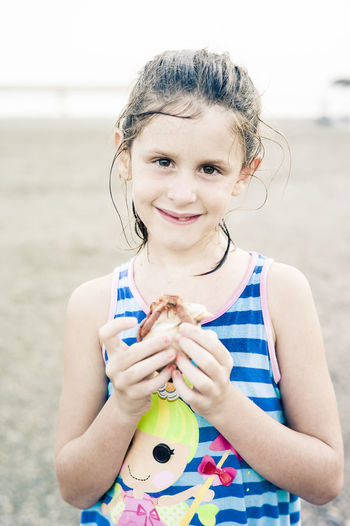 Girl in blue holding a hermit crab she caught on the beach Rockpooling Beach Casual Clothing Child Childhood Crabbing Emotion Focus On Foreground Front View Girls Hermit Crab Hermit Crab Shells Holding Innocence Leisure Activity Looking At Camera One Person Outdoors Portrait Pre-adolescent Child Real People Sea Life Seaside Smiling Waist Up