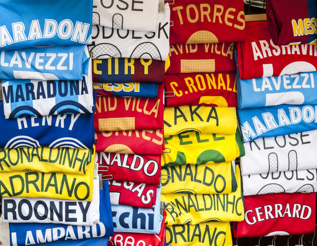 Cheap football shirts for sale in a street market Close-up Football Fever Football Shirts Market Multi Colored Names TEAMS Text