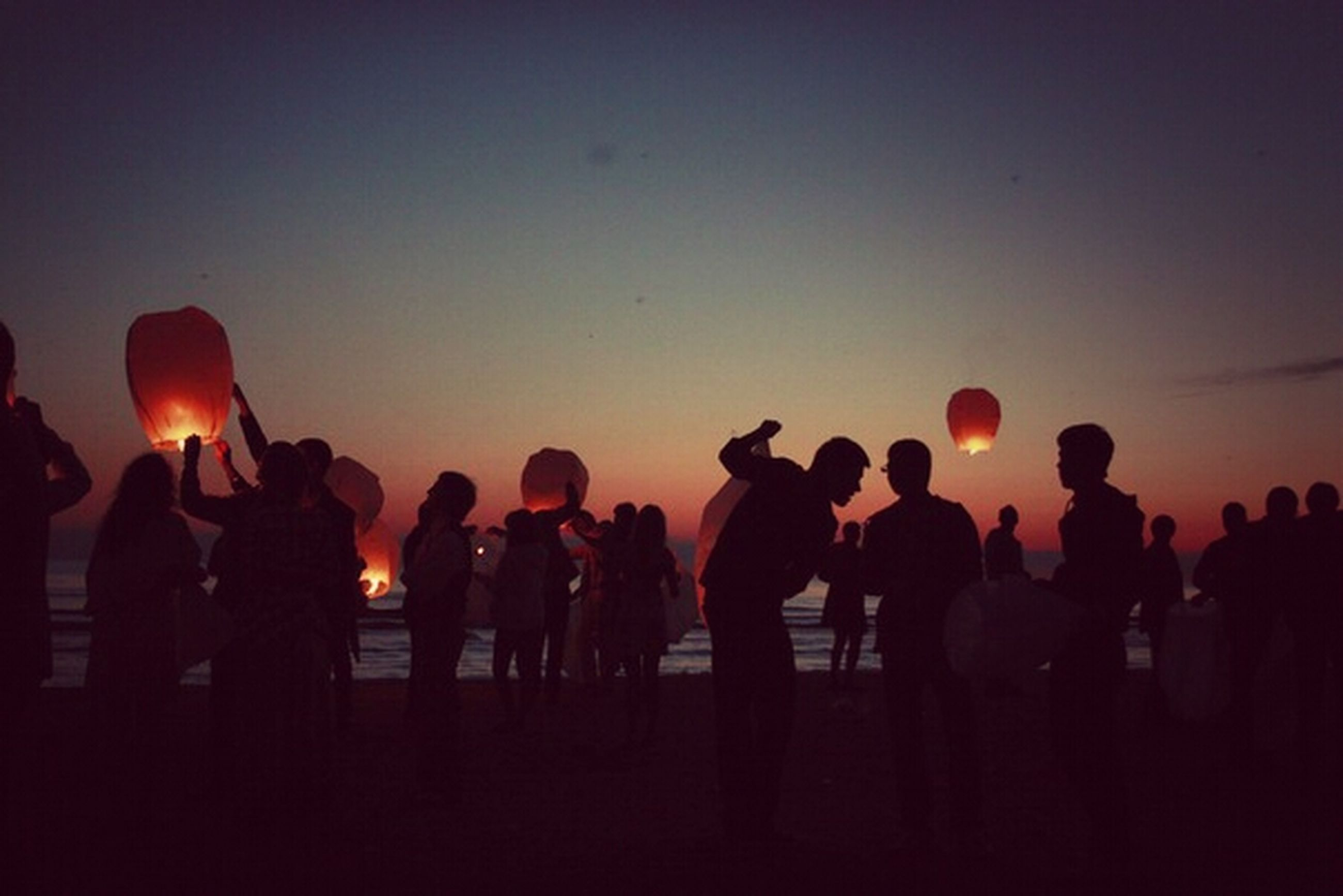 sunset, silhouette, men, large group of people, lifestyles, copy space, leisure activity, orange color, person, clear sky, togetherness, illuminated, standing, sky, dusk, enjoyment, dark, medium group of people, outdoors