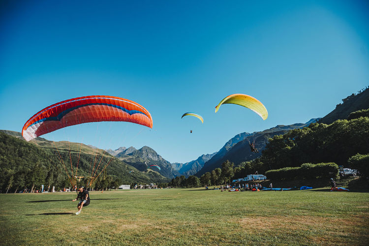 People paragliding against blue sky