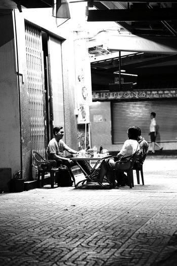 Men sitting on street in city