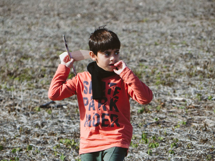 Boy holding model airplane on land