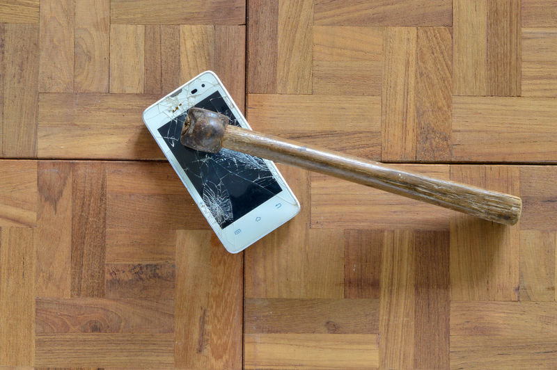 Broken smart phone with hummer Wood - Material Indoors  Wood No People Hardwood Floor High Angle View Directly Above Flooring Table Brown Social Issues Metal Still Life Warning Sign Sign Communication Protection Security Safety Door Wood Grain Steel