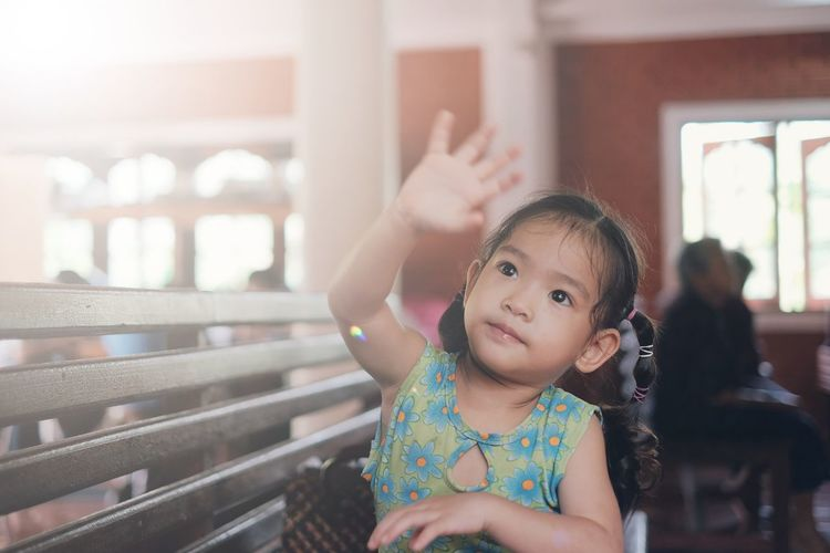 Cute girl looking away while gesturing at home