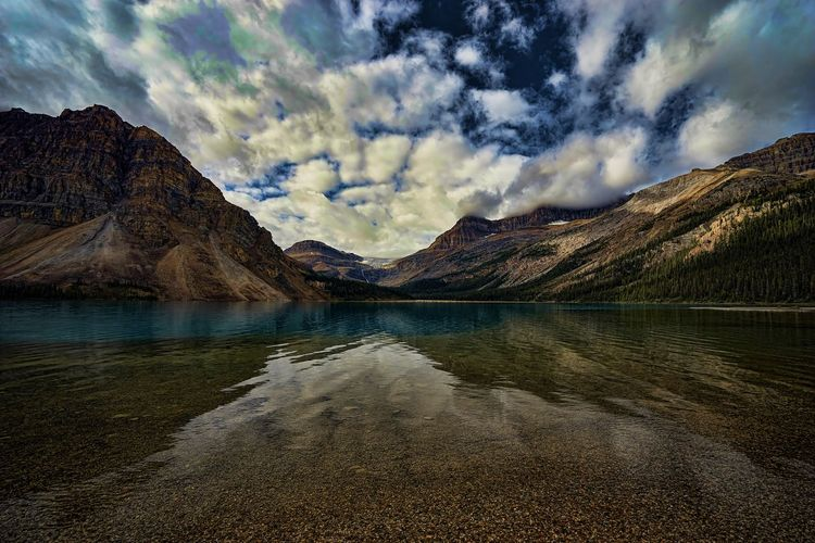 Scenic view of lake and mountains against dramatic sky