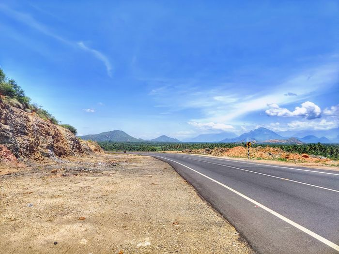 Road leading towards mountains against blue sky
