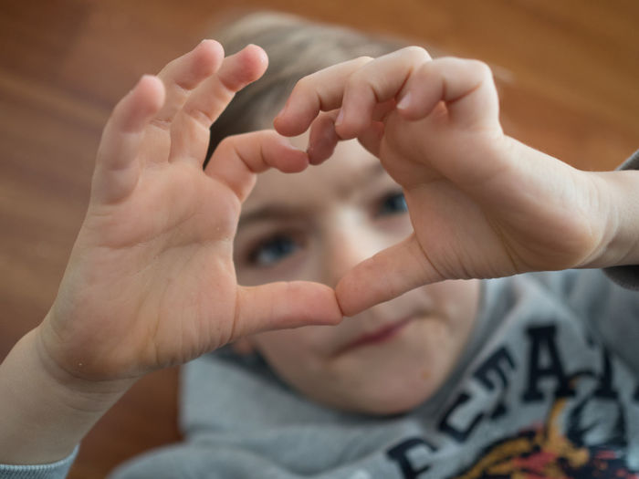 Close-up of boy forming heart shape with hands