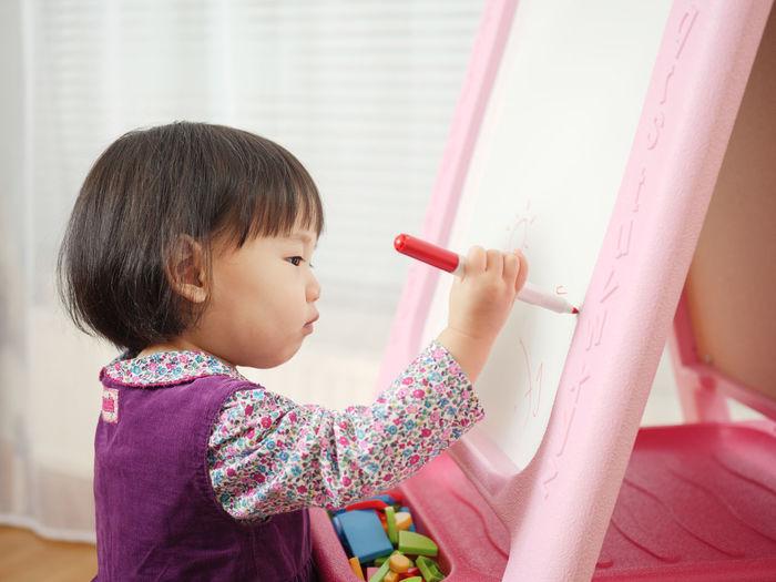 Cute Girl Writing In Whiteboard At Home