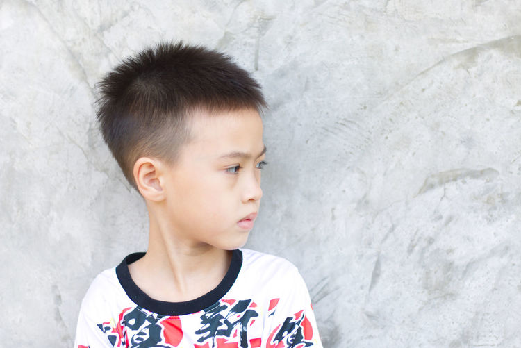 Portrait of boy looking away against wall