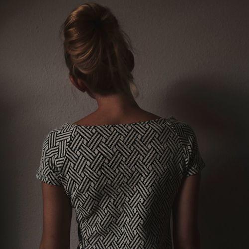 Rear view of woman facing wall