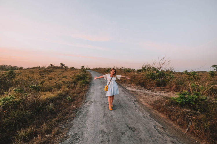 Full length of woman standing on road against sky during sunset