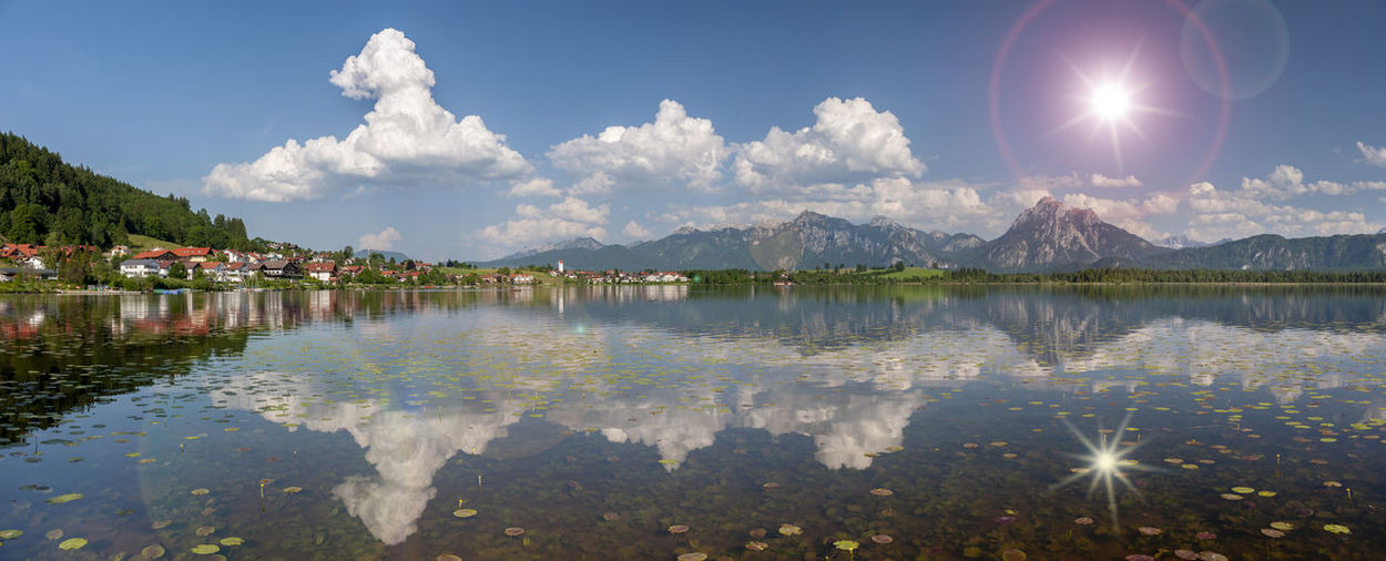 Panoramic view of lake and mountains against bright sun