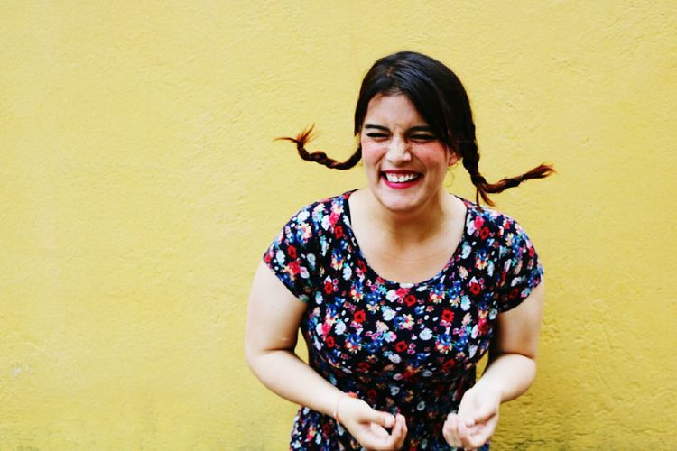 Cheerful woman standing against wall
