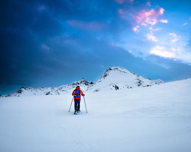 Rear view of person skiing on snowcapped mountain against cloudy sky