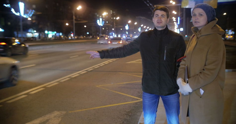 Rear view of friends standing on road in city at night