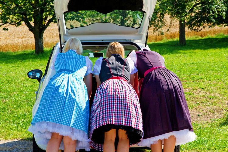 Rear View Of Women In Traditional Clothing Looking In Car Trunk At Park