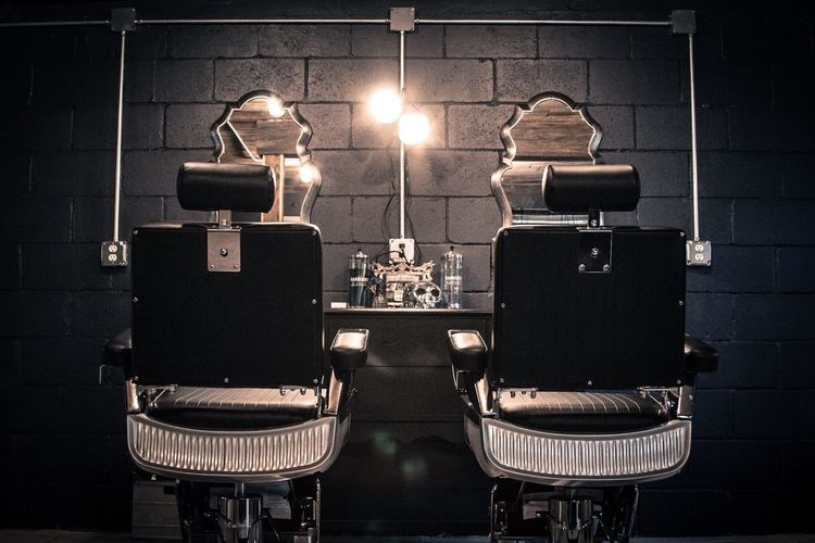 Empty Chairs At Illuminated Barber Shop