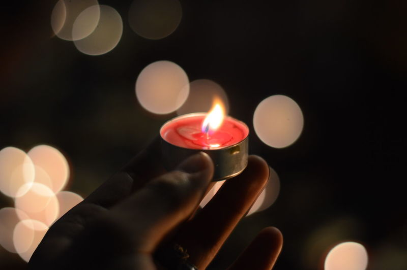 Close-up of hand holding tea light candle against black background