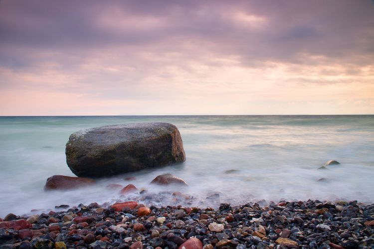 big boulders sticking out from smooth wavy sea. pink horizon with first hot sun style toned effect