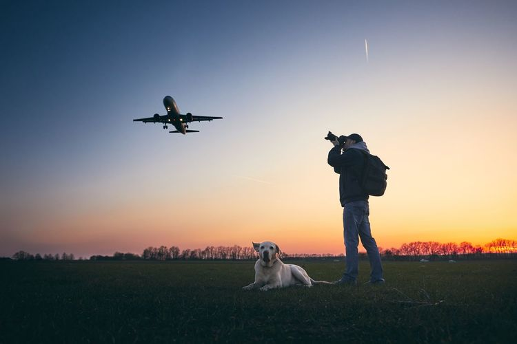 Mid adult man photographing airplane while standing by dog on field against sky during sunset